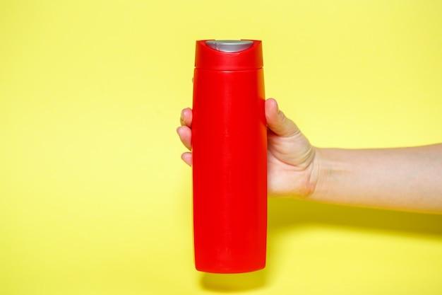 Красная бутылка в руках с гелевым шампунем или жидким мылом на желтом фоне