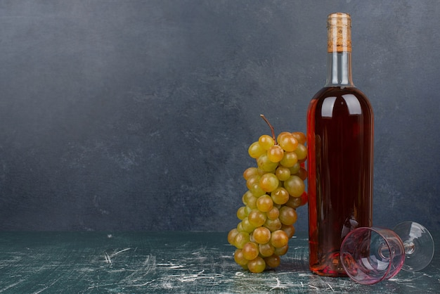 Red bottle with empty glass and grapes