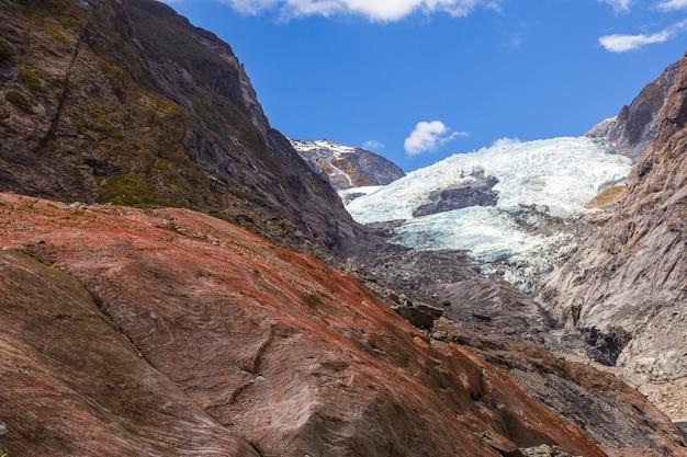 Красный валун на фоне ледника вид на ледник франца иосифа в новой зеландии