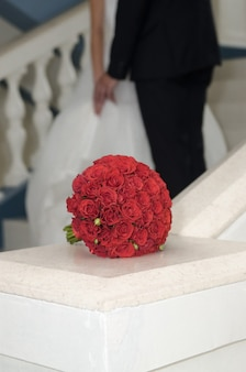 Red bouquet of roses on the background of the newlyweds