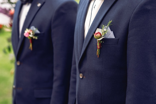 Red boutonnieres pinned to the jackets of groomsmen