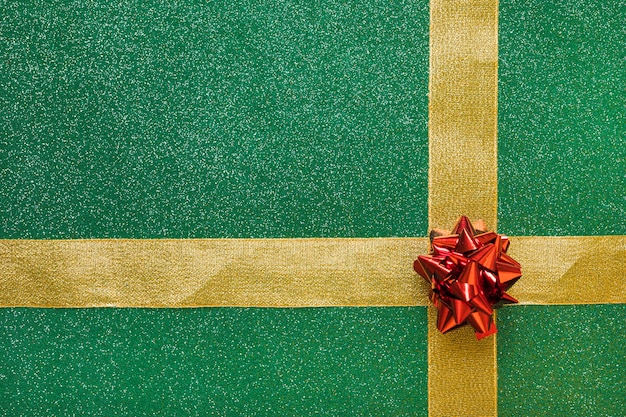 緑色の背景に付いた赤い弓と黄金のリボン