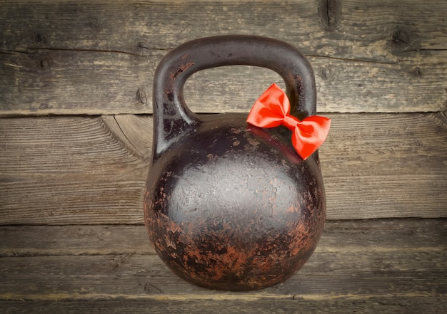 Red bow on old rusty kettlebell over wooden table