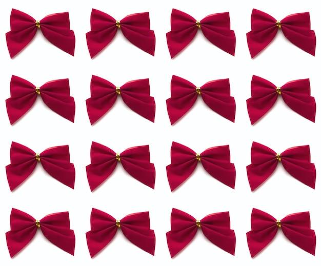 白い背景で隔離の赤い弓のシームレスなパターン