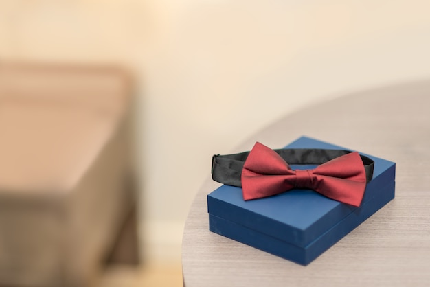 Red bow tie on blue box blur background, set of men's stylish vintage clothing.