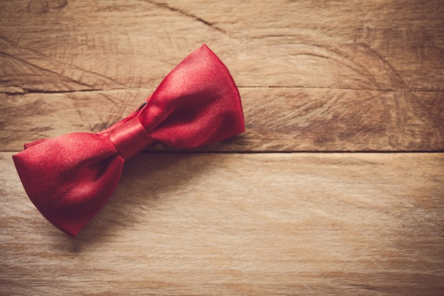 Red bow tie placed on wooden floor.