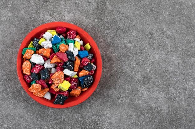 Ciotola rossa di caramelle di pietra colorate su pietra.