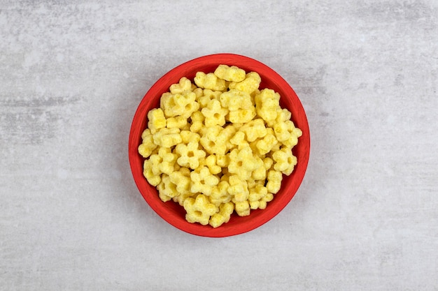 Red bowl full of delicious corn flakes on stone.