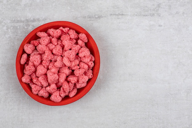 石のテーブルにピンクのシリアルがいっぱい入った赤いボウル。