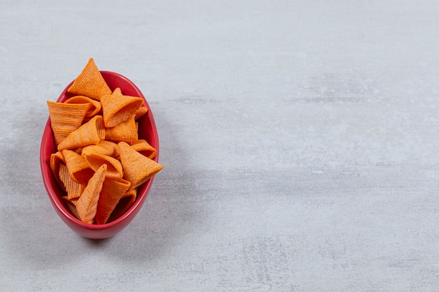 Red bowl full with spicy hot chips.