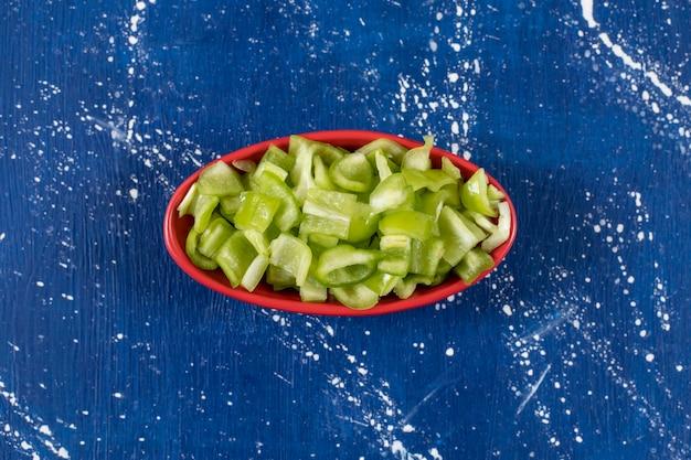 Ciotola rossa di peperoni verdi freschi affettati sulla superficie di marmo