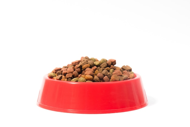 Red bowl with dry animal food for cats or dogs on white