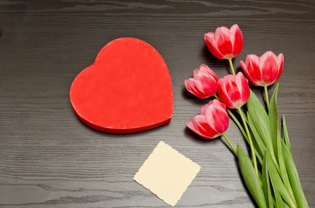 ハートの形の赤いボックス、きれいなカード、ピンクのチューリップ。黒いテーブル。トップビュー、テキスト用のスペース