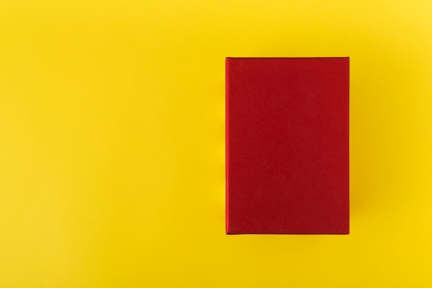 Красная коробка на желтом фоне вид сверху. красный прямоугольник на желтом фоне. скопируйте пространство. макет