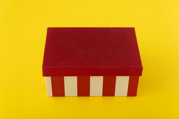 Красная коробка с белыми полосами на желтом фоне. праздничная упаковка.