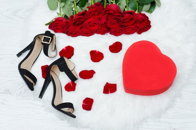 Red boxes in heart shape, black shoes and a bouquet of red roses on a white fur