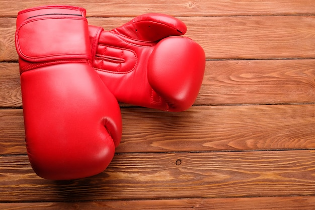 Red boxing gloves on a wooden background