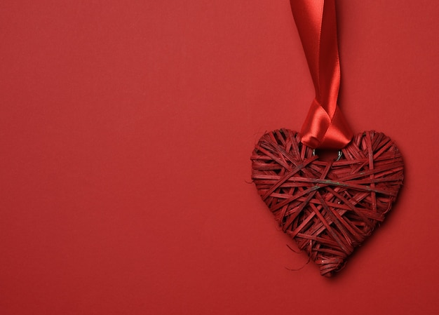 Red braided heart and twisted silk ribbon on a red background, copy space