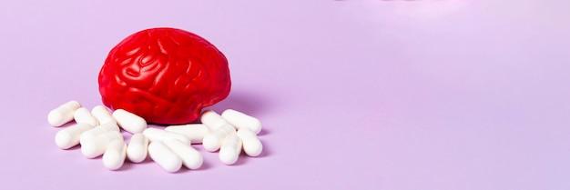 Красный мозг на розовой поверхности с белыми таблетками. таблетки для мозга. лечение мозга.