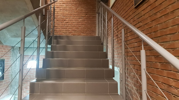 금속 난간이 있는 로프트 스타일의 현대적인 계단이 있는 붉은 벽돌 건물. 계단은 건물을 장식합니다. 현대적인 계단. 강철 난간. 관점에서 계단입니다.
