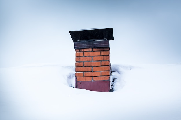 Red brick chimney with iron chimney cap on the roof in snow