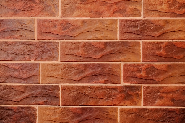 Red brick wall. decorative brick with artificial defects and cracks. texture of decorative tiles in form of brick