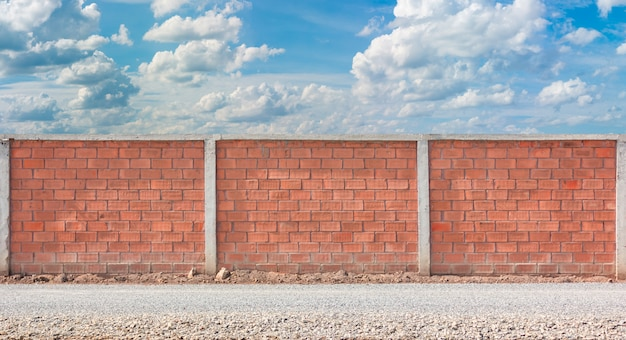 Red brick wall fence with blue sky background