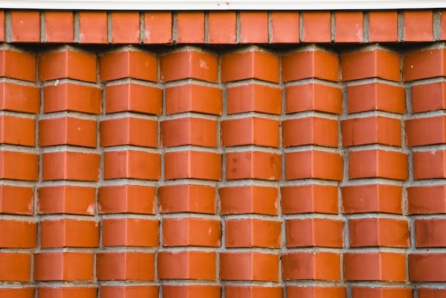 斜めに角張ったレンガの赤レンガの壁。茶色の角レンガの幾何学的な背景画像。白いコーニスの下で上記の滑らかなレンガ造りの化合物。