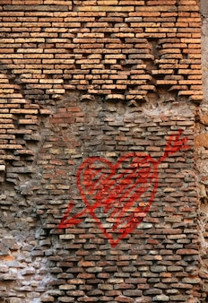 Red brick wall texture grunge background with heart graffiti