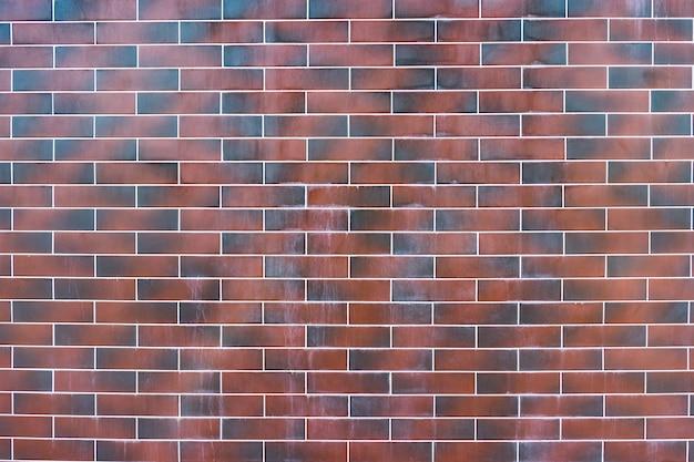 赤レンガの壁。白い詰物が付いている暗い茶色と赤レンガのテクスチャ