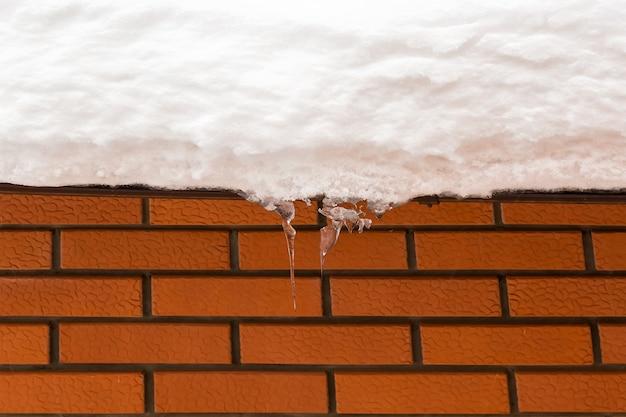 붉은 벽돌 벽입니다. 조직. 눈 지붕에 홈통입니다. 눈 덮인 지붕에 매달려 있는 고드름. 위험이 지붕에 매달려 있습니다.