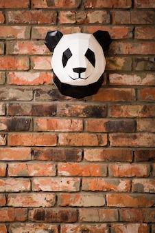 パンダのクマの姿で赤レンガの壁