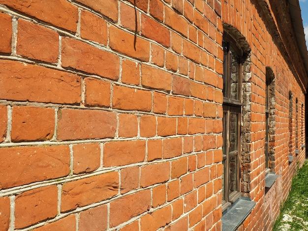 遠くに伸びる窓のある赤レンガの壁