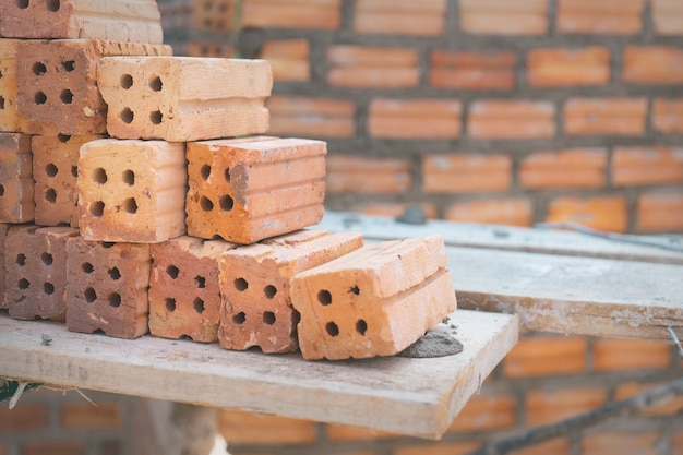 Red bricks used for construction on brick wall background.