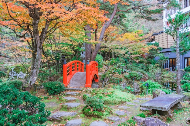 Red bridge in japanese green park with autumn color leaves, japanese autumn fall