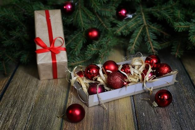 木の床にクリスマスツリーの枝を飾るために赤く明るいボール
