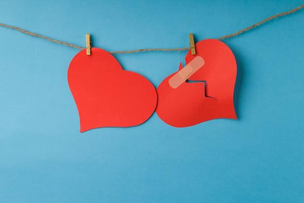 赤い失恋と心がロープにぶら下がっています。