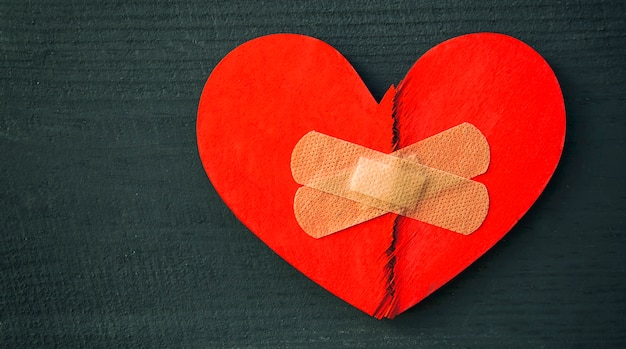 Red broken wooden heart taped by a patch