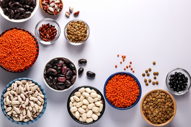 Red and brown lentils, black, brown and white beans are legumes that contain a lot of protein are located in bowls on white background