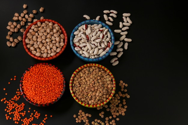 Red and brown lentils, chickpeas and white beans are legumes that contain a lot of protein are located on a dark background in bowls, horizontal orientation, top view