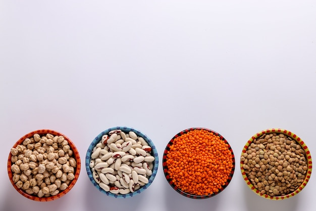 Red and brown lentils, chickpeas and white beans are legumes that contain a lot of protein are located on a white background in bowls, horizontal orientation, copy space
