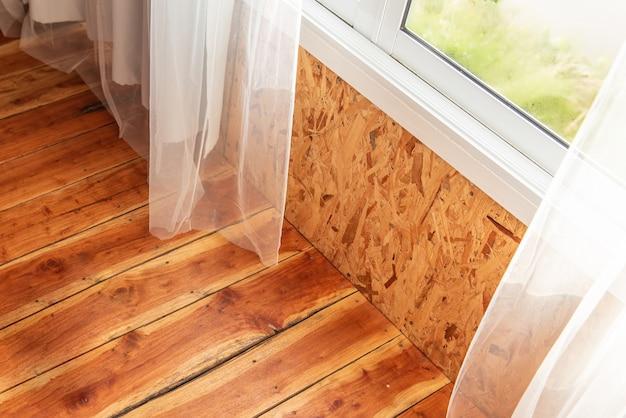 붉은 갈색 쪽모이 세공 마루 자연이 내려다 보이는 창문과 흰색 커튼이있는 방