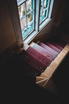 Red and brown staircase near white framed glass window