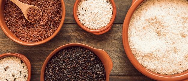 Rosso; riso bianco e marrone in ciotole su fondo in legno