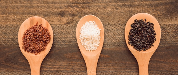 Red; brown and white rice on spoon over wooden background