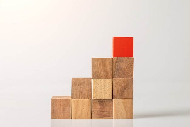 Red and brown wooden geometric shapes cube isolated on a white wall