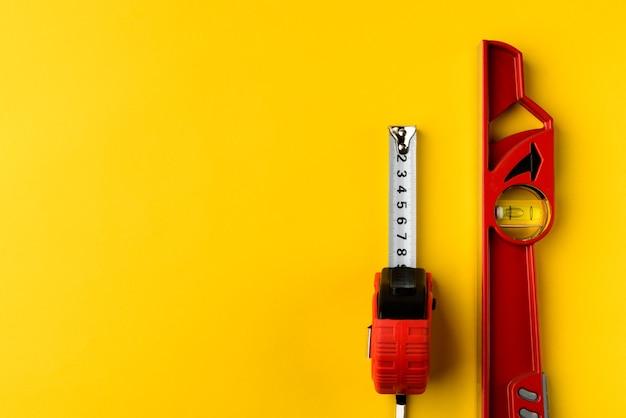 赤い建物のレベルと黄色の背景に巻尺。