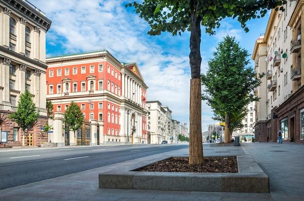 Красное здание мэрии москвы на тверской улице и птицы в небе летним солнечным утром