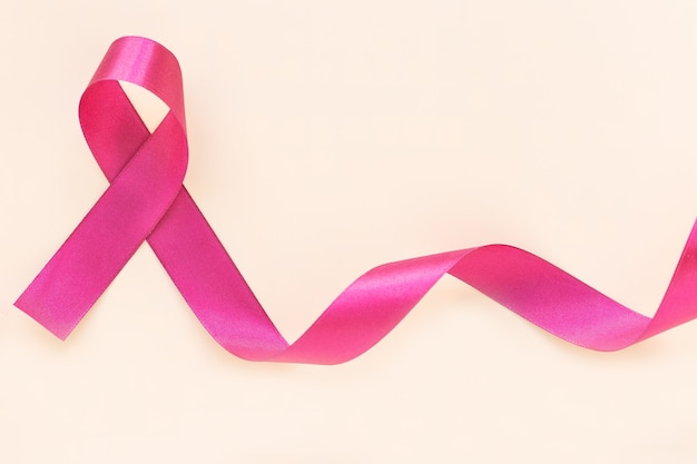 Red burgundy ribbon bow curl on isolated pastel beige wall with copy space, symbol of multiple myeloma or plasma cell cancer awareness.