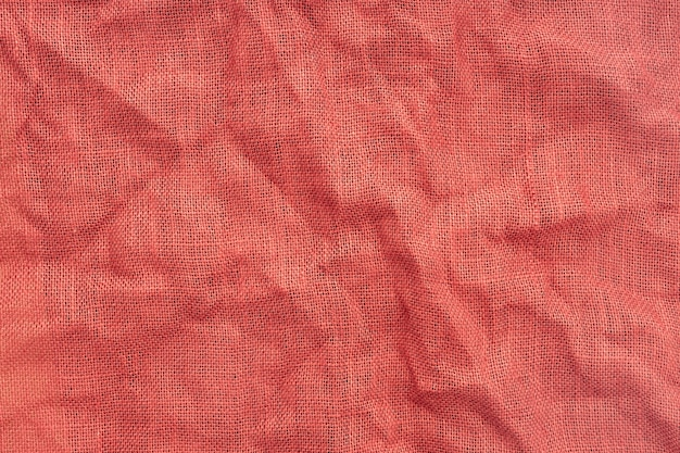 Red burlap fabric with wrinkles background texture. full frame